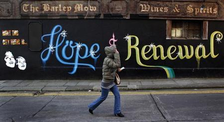 A woman walks past graffiti on the side of a building in Dublin December 5, 2011. REUTERS/Cathal McNaughton