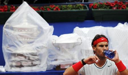 Spain's Rafael Nadal drinks during a break in play in his men's singles final match against compatriot Nicolas Almagro in the Barcelona Open tennis tournament, as trophies are covered with plastic sheets to keep them dry from the rain, in Barcelona April 28, 2013. REUTERS/Albert Gea