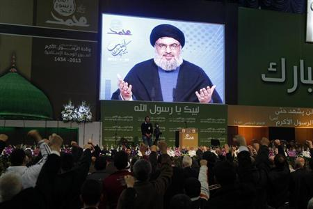Lebanon's Hezbollah leader Sayyed Hassan Nasrallah addresses supporters from a screen during a rally to commemorate the birth of Prophet Mohammad in Beirut's suburbs, January 25, 2013. REUTERS/Sharif Karim