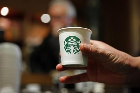 A barista holds a cup of coffee at Starbucks' Vigo Street branch in Mayfair, central London January 11, 2013. REUTERS/Stefan Wermuth