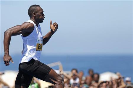 Jamaican Olympic gold medallist Usain Bolt runs to win the ''Mano a Mano Men's 150 metres'' challenge on Copacabana beach in Rio de Janeiro March 31, 2013. REUTERS/Sergio Moraes