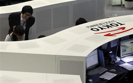 Tokyo Stock Exchange (TSE) employees work at the bourse at TSE in Tokyo April 24, 2013. REUTERS/Yuya Shino