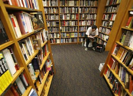 A man reads inside a book shop in Singapore December 1, 2007. REUTERS/Vivek Prakash/Files