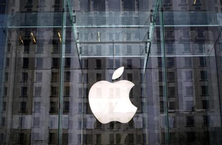 The Apple logo hangs inside the glass entrance to the Apple Store on 5th Avenue in New York City, April 4, 2013. REUTERS/Mike Segar/Files