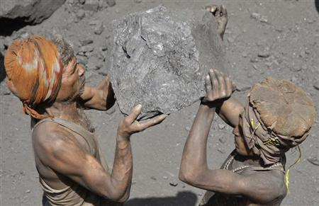 Labourers carry coal to load onto a truck at a coal yard on the outskirts of Allahabad March 24, 2012. REUTERS/Jitendra Prakash/Files