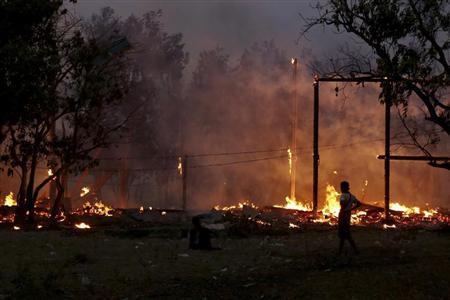 A man looks at buildings on fire during riots at Oakkan village, 100 km (60 miles) north of Yangon April 30, 2013. REUTERS/Stringer