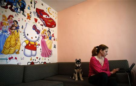 Bulgarian Radostina Petkova, 21, partner of Alexander Angelov works on her laptop inside the living room of their apartment in the town of Vratsa, some 110 km (68 miles) north of Sofia, April 10, 2013. REUTERS/Stoyan Nenov
