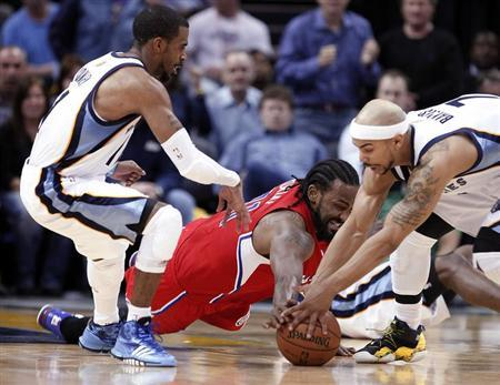 Los Angeles Clippers center Ronny Turiaf fights for a loose ball against Memphis Grizzlies guards Jerryd Bayless (R) and Mike Conley (L) during second half action of game three in the Western Conference quarterfinals of the NBA playoffs in Memphis, Tennessee April 25, 2013. REUTERS/Lance Murphey