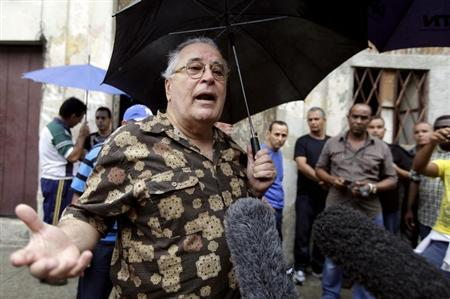 Elizardo Sanchez, spokesman for the independent Cuban Commission on Human Rights, talks to reporters during his arrival at Laura Pollan house in Havana October 15, 2011. REUTERS/Enrique De La Osa