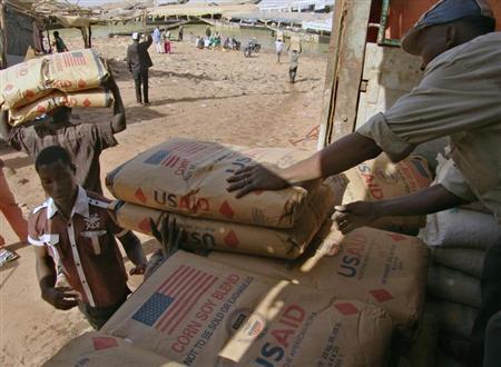 Men transport humanitarian food aid onto pirogues at Mopti February 4, 2013. REUTERS/Alain Amontchi