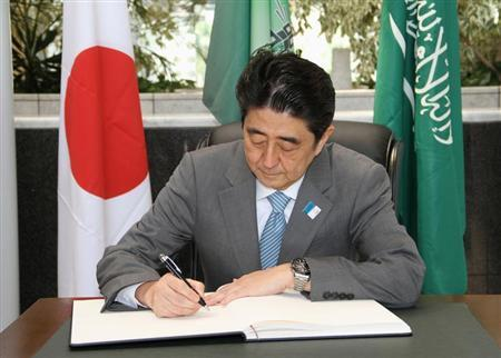 Japanese Prime Minister Shinzo Abe signs a business agreement after a conference at King Abdulaziz University in Jeddah, May 1, 2013. REUTERS/Susan Baaghil