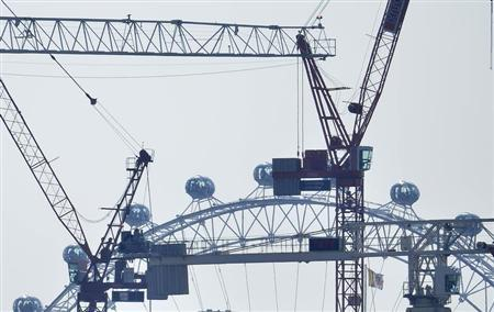 Construction cranes are seen near the London Eye wheel in central London April 25, 2013. REUTERS/Toby Melville