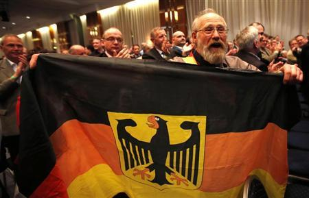 A delegate of Germany's anti-euro party ''Alternative fuer Deutschland'' (Alternative for Germany) waves a German flag during the first party congress in Berlin April 14, 2013. REUTERS/Fabrizio Bensch