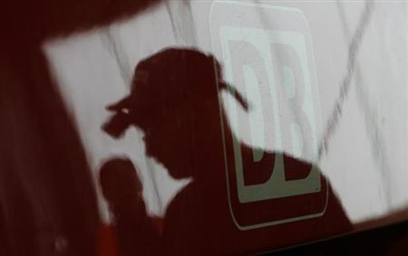 A technician of Bombardier is reflected next to the logo of German 'Deutsche Bahn' painted on a new 'BR 422' public train at the plant in Hennigsdorf, near Berlin, November 8, 2007. REUTERS/Tobias Schwarz