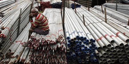 A worker sits on steel pipes at a steel pipes market in Mumbai July 11, 2008. REUTERS/Arko Datta/Files