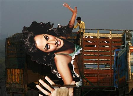 A worker pulls a publicity cut-out of a Bollywood movie in Mumbai December 16, 2009. REUTERS/Arko Datta
