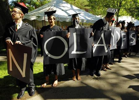 Students hold letters spelling out ''No layoffs'' during the 361st Commencement Exercises at Harvard University in Cambridge, Massachusetts May 24, 2012. REUTERS/Brian Snyder