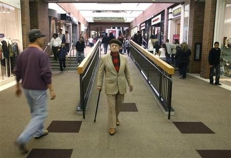 An elderly man walks with his cane amid shoppers at the Glendale Galleria shopping mall on Black Friday in Glendale, California November 28, 2008. REUTERS/Fred Prouser