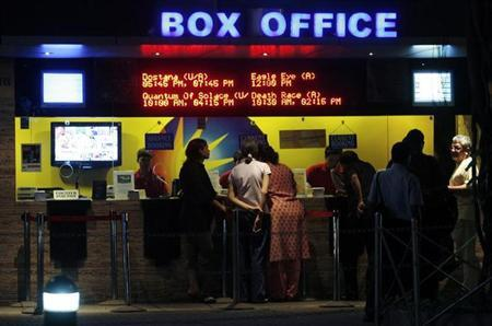People buy tickets at a counter in a multiplex movie theatre in Mumbai November 22, 2008. REUTERS/Arko Datta/Files