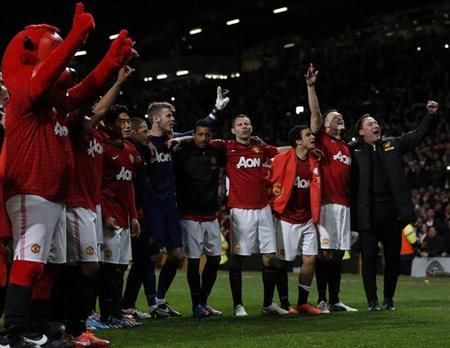 Manchester United players and staff celebrate after they clinched the English Premier League soccer title with a win against Aston Villa at Old Trafford in Manchester, northern England, April 22, 2013. REUTERS/Phil Noble