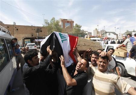 Residents carry the coffin of a victim, who was killed in a bomb attack, during a funeral in Najaf, 160 km (100 miles) south of Baghdad, April 27, 2013. REUTERS/Haider Ala