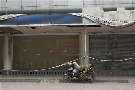 A man sleeps on a motorbike in front of a closed supermarket in Hanoi April 25, 2013. REUTERS/Kham