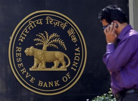 A man makes a phone call while standing near a Reserve Bank of India (RBI) crest at the RBI headquarters in Mumbai January 29, 2013. REUTERS/Vivek Prakash