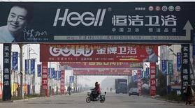 A motorist drives under advertisement boards at the business area of Ruzhou county, China's central Henan province, December 18, 2012. REUTERS/Aly Song