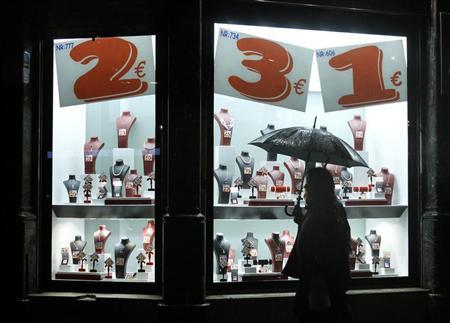 People walk past the shop window of a jewelry store in central Barcelona November 27, 2012. REUTERS/Albert Gea