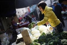 A woman holds up cauliflowers at a stall inside a market in Shanghai December 9, 2011. REUTERS/Aly Song