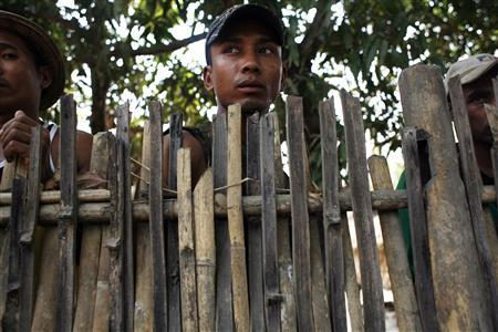 Muslim men from Win Kite village look from behind the fence which residents built to protect their village from mob attacks May 2, 2013. REUTERS/Minzayar