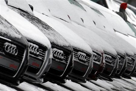 A man walks between Audi cars for sale which are covered with snow at a dealer in Ingolstadt January 16, 2013. REUTERS/Michael Dalder