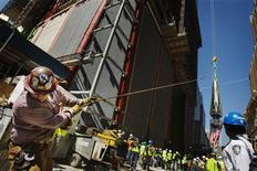 Metalúrgico usa corda para estabilizar peça com uma bandeira norte-americana pendurada, antes de ser elevada para o topo do One World Trade Center, em Nova York. O nível de emprego nos Estados Unidos aumentou mais do que o esperado em abril, levando a taxa de desemprego para uma mínima de quatro anos de 7,5 por cento, o que pode ajudar a abrandar os temores de uma forte desaceleração na economia. 02/05/2013 REUTERS/Lucas Jackson