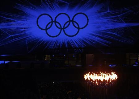 The Olympic Rings are seen behind the Olympic Torch during the closing ceremony of the London 2012 Olympic Games at the Olympic Stadium August 12, 2012. REUTERS/Luke Macgregor/Files