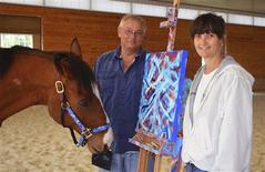 Metro, a 10-year-old retired bay thoroughbred horse stands with owners Ron Krajewski and Wendy Krajewski (R) and one of his paintings at Motter's Station Stables in Rocky Ridge, Maryland May 2, 2013. Since giving up the track, Metro has begun a successful painting career that has netted about $20,000 in four months. REUTERS/Jeffrey B. Roth