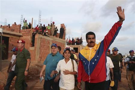 Venezuela's President Nicolas Maduro (R) waves to supporters during a visit to a housing development in Maracaibo, in this picture provided by Miraflores Palace on April 26, 2013. REUTERS/Miraflores Palace/Handout