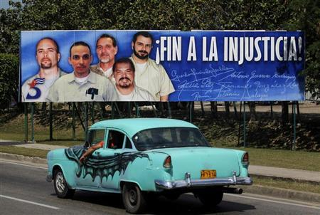 A car drives past a poster of the five Cuban prisoners in U.S. jails, in Havana March 30, 2012. REUTERS/Enrique de la Osa