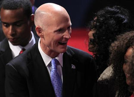 Florida Governor Rick Scott greets an attendee in the audience before the start of the final U.S. presidential debate between Republican presidential nominee Mitt Romney and President Barack Obama in Boca Raton, Florida, October 22, 2012. REUTERS/Joe Skipper