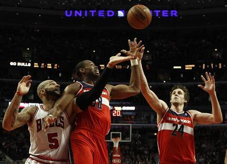 Washington Wizards' Jason Collins (C) and Wizards' Jan Vesely (R) battle for a rebound against Chicago Bulls' Carlos Boozer during the first half of their NBA basketball game in Chicago, Illinois, April 17, 2013. REUTERS/Jim Young
