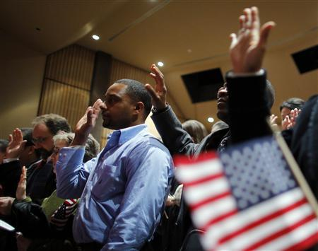Over 90 immigrants representing over 40 countries take the oath of citizenship during a naturalization ceremony to become new citizens of the U.S. at Boston College in Chestnut Hill, Massachusetts March 21, 2013. REUTERS/Brian Snyder