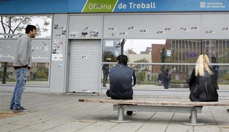 People wait for an employment office to open in Badalona, near Barcelona, April 25, 2013. The stickers on the wall read, ''Unemployment''. REUTERS/Albert Gea