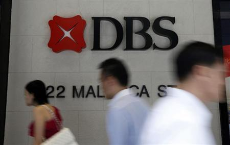 Office workers pass a logo of Development Bank of Singapore (DBS) in the central business district in Singapore April 30, 2013. REUTERS/Edgar Su