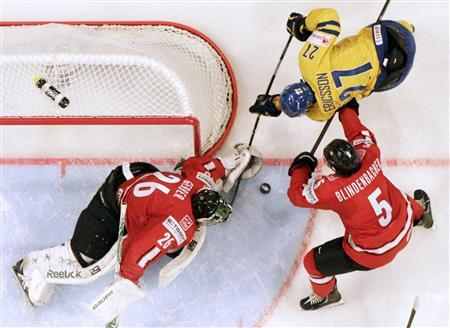 Switzerland's goalie Martin Gerber (L) and Severin Blindenbacher (R) fight for the puck with Sweden's Jimmie Ericsson during their 2013 IIHF Ice Hockey World Championship preliminary round match at the Globe Arena in Stockholm May 3, 2013. REUTERS/Arnd Wiegmann
