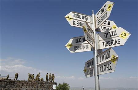 Israeli soldiers stand near signs pointing out distances to different cities at an observation point on Mount Bental in the Israeli-occupied Golan Heights May 5, 2013.U.N. REUTERS/Baz Ratner