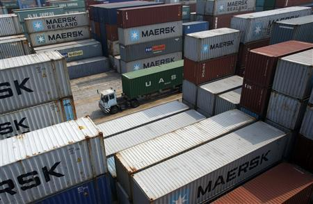 A trailer truck drives past containers at a port in Ningbo, Zhejiang province, April 10, 2013. REUTERS/William Hong