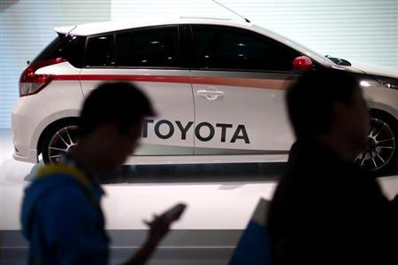People look at a Toyota car during the 15th Shanghai International Automobile Industry Exhibition in Shanghai April 21, 2013. REUTERS/Carlos Barria