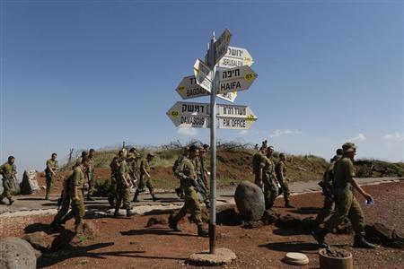 Israeli soldiers walk past signs pointing out distances to different cities at an observation point on Mount Bental in the Israeli-occupied Golan Heights May 5, 2013.U.N. Secretary-General Ban Ki-moon on Sunday voiced alarm at reports Israel has struck targets inside Syria, but said the United Nations was unable to confirm whether any such attacks had taken place. REUTERS-Baz Ratner
