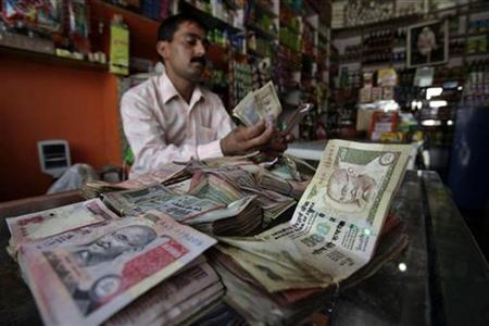 A shopkeeper counts Indian currency notes inside his shop in Jammu July 14, 2010. REUTERS/Mukesh Gupta/Files