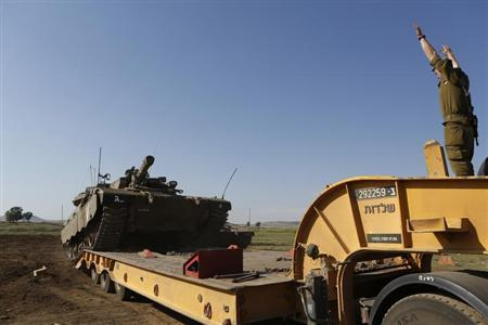 An Israeli soldier signals a tank off a truck near the Israeli Syrian border in the Israeli-occupied Golan Heights May 5, 2013. REUTERS/Baz Ratner