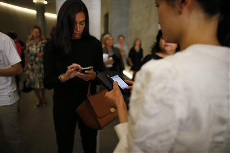 Women use their iPhones during Milan Fashion Week September 20, 2012. Picture taken September 20, 2012. REUTERS/Stefano Rellandini